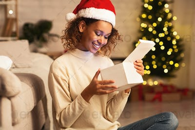 African-american girl looking inside Christmas present at home