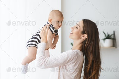 Millennial mom playing with her newborn baby at home