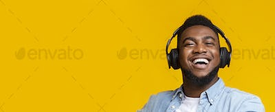 African american man in modern headphones smiling on yellow background