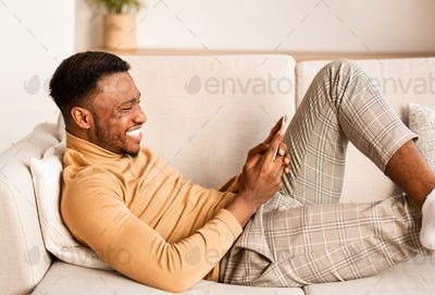 Relaxed Guy Using Smartphone Lying On Sofa At Home