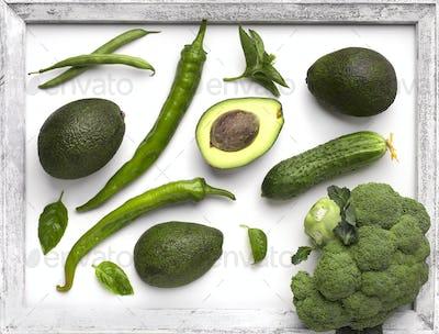 Green organic vegetables inside wooden border on white