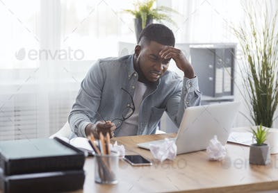 Annoyed black employee looking at laptop screen with despair