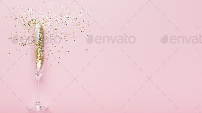 Gold confetti poured out of champagne glass on pink