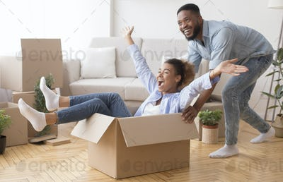 Excited Man Riding Woman In Moving Box In New House