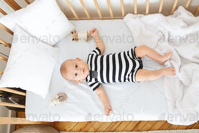 Adorable newborn baby lying in crib and looking at camera