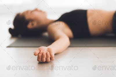 Young woman practicing yoga in corps pose
