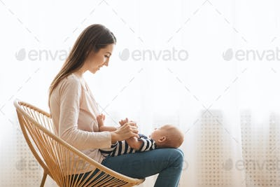 Mother playing with her baby while sitting in wicker chair
