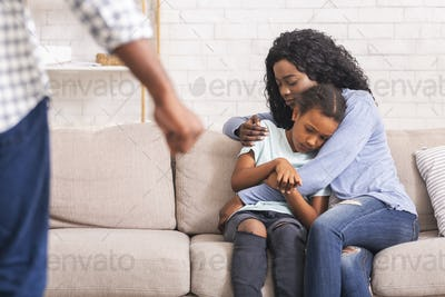 Afro mother and daughter suffering from domestic violence of father