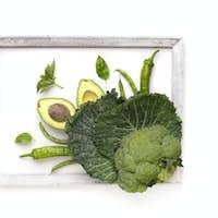 Green vegetables inside frame on white background