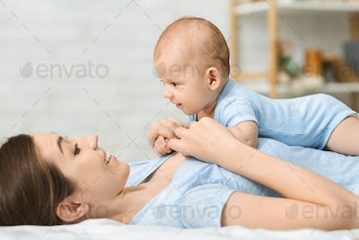 Cute newborn baby relaxing on bed with mom
