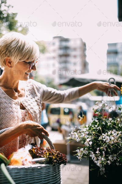 Attractive senior woman shopping in an outdoors fresh flowers market