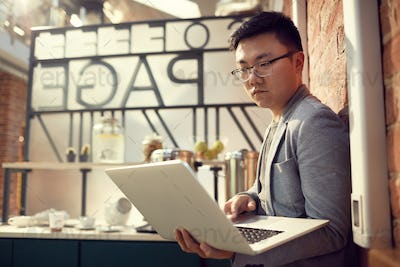 Asian Entrepreneur Holding laptop
