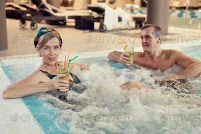 Modern Senior Couple Enjoying Hot Tub at Resort