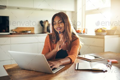 Young woman working online in her kitchen at home