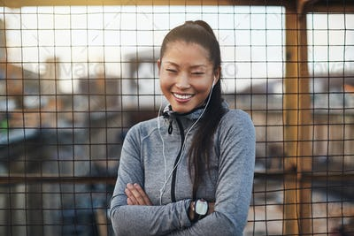 Sporty Asian woman standing with her arms crossed outdoors