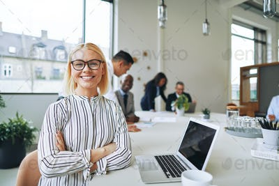 Smiling businesswoman working at boardroom table in an office