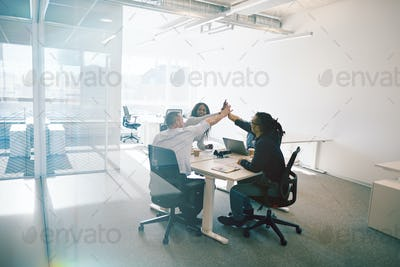 Work colleagues laughing and high fiving during an office meeting