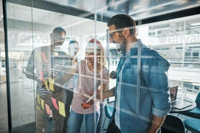 Smiling businesspeople brainstorming on a glass wall with sticky notes