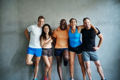 Smiling friends in sportswear standing together in a gym