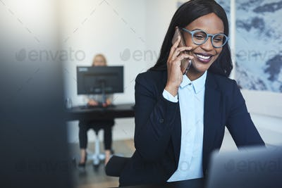 Smiling African American businesswoman talking on a cellphone at work