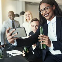 Smiling African American businesswoman taking selfies during after work drinks