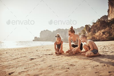 Mother and kids playing in the sand at the beach