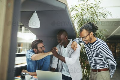 Diverse designers celebrating while working in an office meeting pod