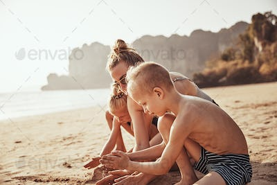 Mother and children building sandcastles together at the beach