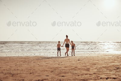 Mother and children holding hands while walking along a beach