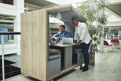 Smiling businessmen working together in an office meeting pod