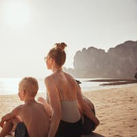Mother and children enjoying the view from a sandy beach