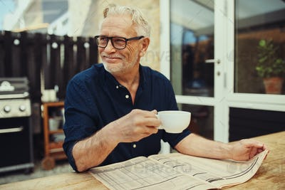 Smiling senior man drinking coffee and reading a newspaper outside