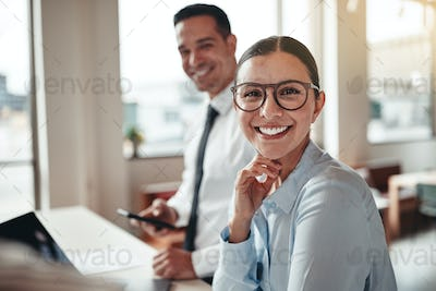 Businesswoman smiling while working with a colleague in an office