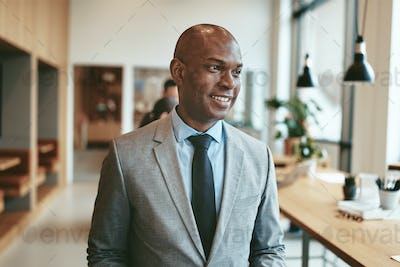 Smiling African American businessman standing in a modern office