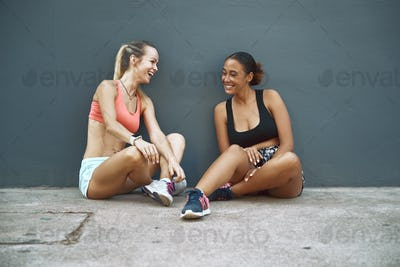 Laughing friends sitting outside taking a break from their workout