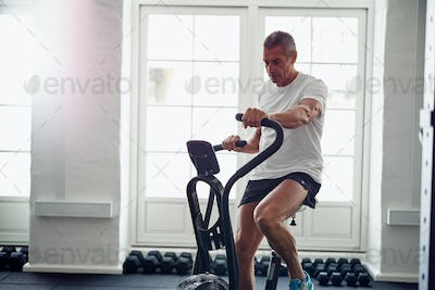 Mature man riding a health club stationary bike