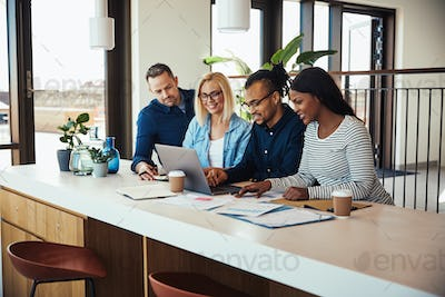 Diverse businesspeople working on a laptop in an office
