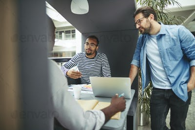 Diverse group of businessmen working together in an office pod