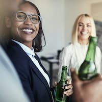 Smiling African American businesswoman talking with colleagues over office drinks