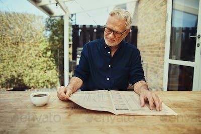 Senior man relaxing outside with a coffee and newspaper