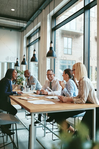 Smiling group of diverse businesspeople meeting together in an office