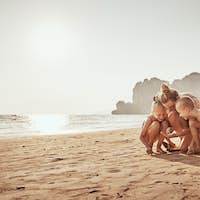 Mom and children playing in the sand at the beach