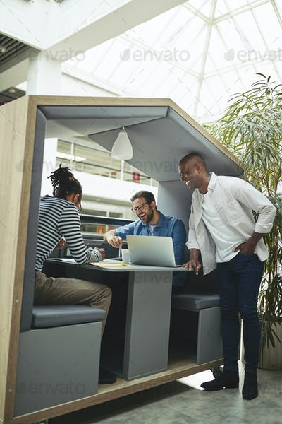 Laughing businessmen meeting together in an office meeting pod