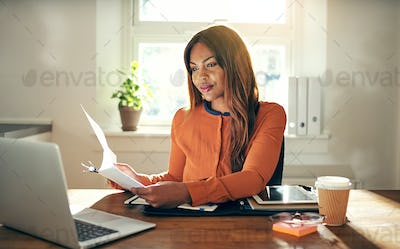 Young female entrepreneur working in her home office reading paperwork