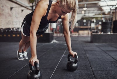 Fit young woman doing pushups with weights in a gym