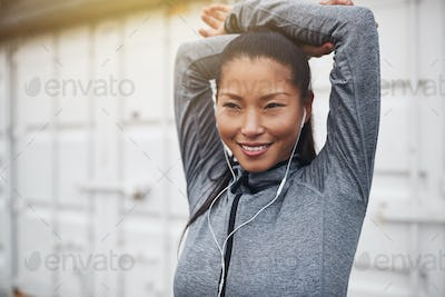 Sporty young Asian woman wearing earphones stretching before jogging