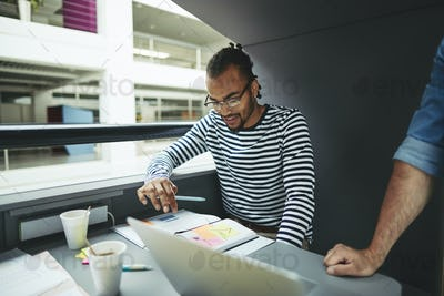 Young African American designer working in an office meeting pod