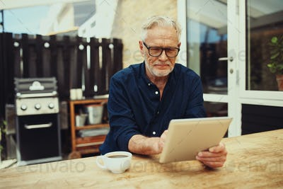 Senior man drinking coffee while using a digital tablet