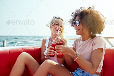 Two young friends laughing over drinks on a boat