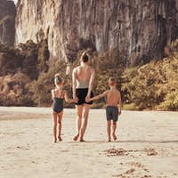 Mom and her two children walking down along sandy beach